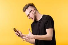 Wtf jonge mens het gillen smartphone het grimassen trekken stock foto
