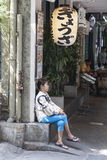 Tired woman taking a break. At the street under the sign with ideograms  in front of japanese restaurant Stock Image