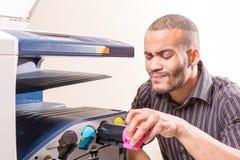 Wątpić afrykańskiego mężczyzna naprawiania copier w biurze Fotografia Stock