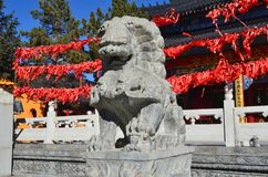 Wudalianchi, China. Sculpture of the mythological lion in front of the entrance to the temple  Zhongling  on the top of extinct Ya Royalty Free Stock Photography