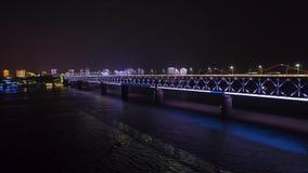WUHAN KINA - MAJ 2, 2017: surr för upplyst bro för cityscape för nattetid flyg- qingchuan arkivfilmer