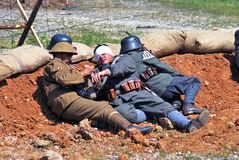 A wunded soldier lays on the ground. Stock Image
