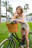 Wunderbare blonde weibliche Aufstellung mit ihrem klassischen Fahrrad an einem Sommertag Stockfotografie