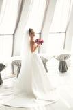 Wunderbare Braut mit einem luxuriösen weißen Kleid, das in der alten Stadt aufwirft lizenzfreies stockbild