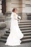 Wunderbare Braut mit einem luxuriösen weißen Kleid, das in der alten Stadt aufwirft lizenzfreie stockbilder