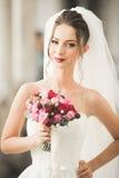 Wunderbare Braut mit einem luxuriösen weißen Kleid, das in der alten Stadt aufwirft stockfotografie