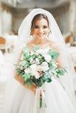 Wunderbare Braut mit einem luxuriösen weißen Kleid und einem Blumenstrauß stockbild