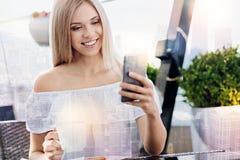 Wunderbare glückliche Frau, die durch Mitteilungen schaut Lizenzfreies Stockbild
