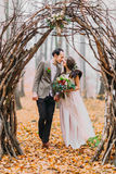 Wunderbare Hochzeitspaare betrachten einander liebevoll unter dem Haselnussbogen im Herbstwald Stockfotografie