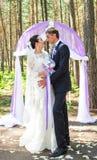 Wunderbare stilvolle reiche glückliche Braut und Bräutigam, die an einer Hochzeitszeremonie im grünen Garten nahe purpurrotem Bog Stockfotos