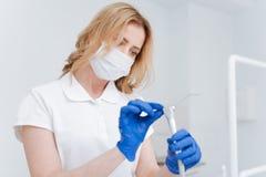 Wunderbarer ordentlicher Zahnarzt, der ihre Ausrüstung säubert Lizenzfreie Stockbilder