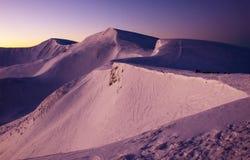 Wunderbarer purpurroter Sonnenaufgang in den Karpaten im Winter Schneebedeckte Gipfel von Winterbergen in den roten Strahlen des  stockfotos