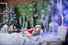 Wunderbarer Weihnachtsstandort mit Nachahmung des Schnees, Eiszapfen, verzierter Weihnachtsbaum, die Schlitten der Kinder, Tannen lizenzfreies stockbild