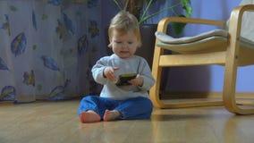 Wunderbares blauäugiges Kind sitzt auf dem Boden und spricht am Handy stock video footage