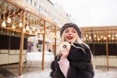 Wunderbares blondes Modell, das leckeres Ingwerplätzchen gegen Licht hält Stockfotografie