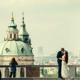 Wunderbares Foto der reisenden Jungvermähltenpaare in Prag Der Bräutigam küsst die Braut in der Backe am Hintergrund lizenzfreies stockfoto
