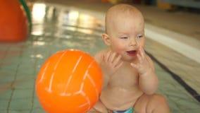 Wunderbares Kind, das mit einem orange Ball sitzt im warmen Pool der Kinder an einem Wasserpark spielt stock video footage