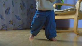 Wunderbares Kind macht erste zögernde Schritte stock footage