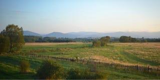 Wunderbares Panorama der Felder, der Berge und des Himmels Stockfotografie