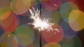 Wunderkerze über Weihnachtshintergrund mit unscharfer Farbe beleuchtet HD stock video