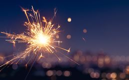 Wunderkerze mit unscharfem Stadtlichthintergrund stockfotografie