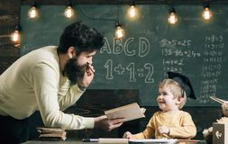 Wunderkind and genius concept. Father, teacher reading book, teaching kid, son, chalkboard on background. Dad wants to. Grow up genius son. Boy child in royalty free stock image