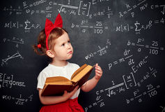 Wunderkind little girl schoolgirl with a book from the blackboar Royalty Free Stock Photography