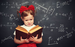 Wunderkind little girl schoolgirl with a book from the blackboar Stock Photography
