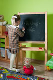 Wunderkind. A little girl writting on the blackboard physical formula Royalty Free Stock Images