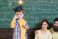 Wunderkindbegrepp Smart barn, wunderkind i doktorand- lock som pekar på hans huvud Pojke som framlägger hans kunskap till mamman Royaltyfri Foto