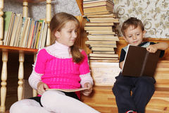 Wunderkinds. The small wunderkind shows something interesting in the book to the big sister Royalty Free Stock Photos