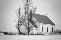 Wunderliche kleine weiße Landkirche, die auf einer Decke des Schnees sitzt lizenzfreie stockbilder