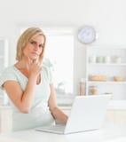 Wundernde blonde Frau, die Notizbuch betrachtet Lizenzfreie Stockfotos