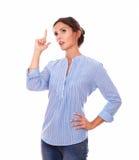Wundernde erwachsene Dame auf der blauen Bluse, die oben schaut Lizenzfreie Stockfotografie