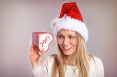 Wundernde Weihnachtsfrau mit einem Sankt-Hut, der eine Geschenkbox hält Stockfotografie