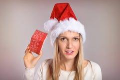Wundernde Weihnachtsfrau mit einem Sankt-Hut, der eine Geschenkbox hält Stockbilder