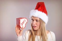 Wundernde Weihnachtsfrau mit einem Sankt-Hut, der eine Geschenkbox hält Stockbild