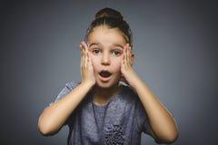 Wunderndes Mädchen Nahaufnahme-Porträt des hübschen Kindes auf grauem Hintergrund Lizenzfreie Stockbilder