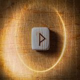 Wunjo. Handmade scandinavian wooden runes on a wooden vintage background in a circle of light. Concept of fortune royalty free stock images