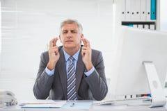 Wunsch des Geschäftsmannes, der seine Finger kreuzt Stockfotos