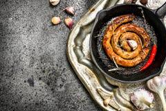 Wurst in einer Bratpfanne mit Peperoni und Knoblauch auf einem Stahlbehälter Lizenzfreie Stockfotos