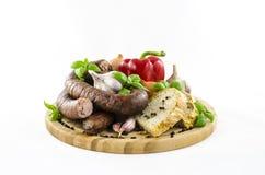 Wurst mit Brot und Gemüse auf hölzernem Brett Lizenzfreies Stockfoto