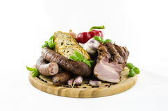 Wurst und Speck mit Gemüse auf hölzernem Brett Stockfoto