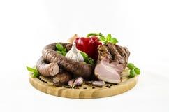Wurst und Speck mit Gemüse auf hölzernem Brett Lizenzfreie Stockfotos