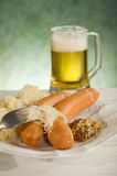 Wurstel sausage with sauerkraut. Mustard and glass of beer Stock Image