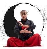 Wushu de pratique de femme sur le plancher avec le signe de Yin Yang Image stock