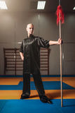 Wushu fighter poses with lance, martial arts. Man in black  cloth poses with blade Stock Photos