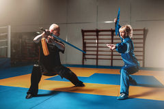 Wushu fighters, man and woman with swords Royalty Free Stock Image