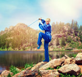 Wushu master with sword against lake and mountains Stock Photography
