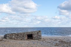 WW2 beach defence building uncovered by tidal surge. Partially buried historic military structure on the coast of England royalty free stock photography